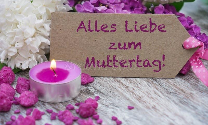 Cartolina d'auguri con i fiori e la candela lilla fotografia stock