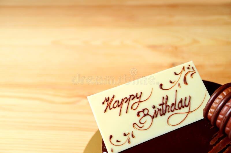 Cartolina d'auguri di buon compleanno fatta da cioccolata bianca decorata sulla torta di compleanno del cioccolato, con lo spazio fotografie stock libere da diritti