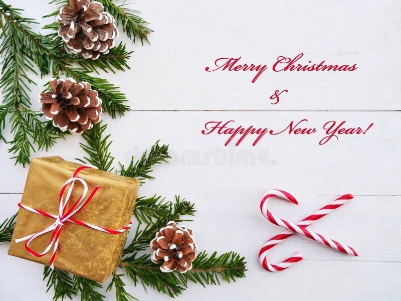Cartolina d'auguri di Buon Natale con il bastoncino di zucchero, il regalo, i coni ed i rami dell'abete sopra la tavola di legno  fotografia stock libera da diritti