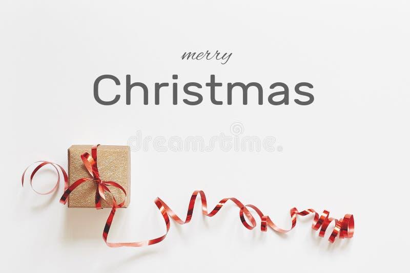 Cartolina d'auguri di Buon Natale Contenitore di regalo con il nastro rosso su fondo bianco con il testo di congratulazione fotografia stock