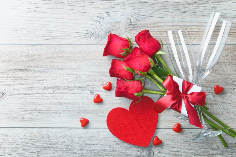 Cartolina d'auguri di giorno di biglietti di S. Valentino, contenitore di regalo, rose rosse e champagne fotografia stock