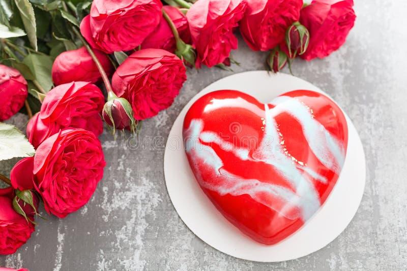 Cartolina d'auguri di giorno o di compleanno di biglietti di S. Valentino Dolce sotto forma di cuore rosso Rose rosse e dessert s fotografie stock libere da diritti