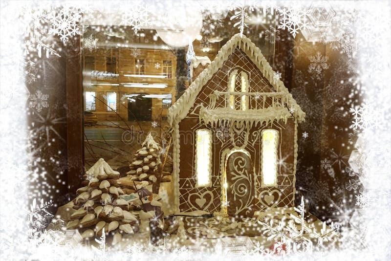 Cartolina d'auguri di Natale con la casa di pan di zenzero e pupazzo di neve nel telaio dei fiocchi di neve bianchi su fondo dell fotografie stock