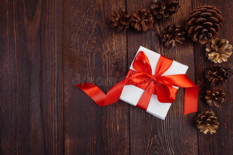 Cartolina d'auguri di natale Contenitore di regalo bianco con il nastro rosso ed urti su un fondo di legno con il posto per il vo fotografie stock