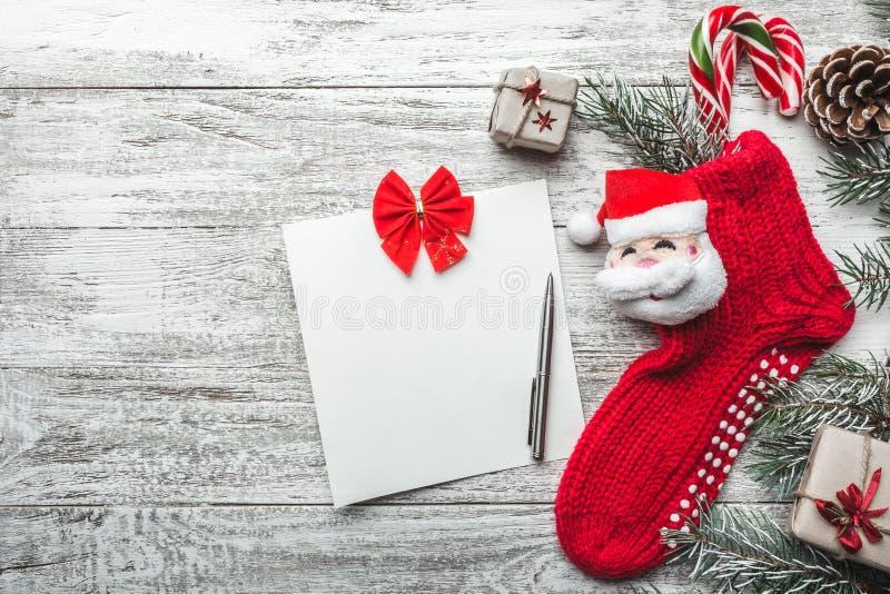 Cartolina d'auguri di natale Fondo di legno, bianco dipinto con un calzino di Natale e Santa Claus Candy ha colorato in  Regalo H fotografia stock