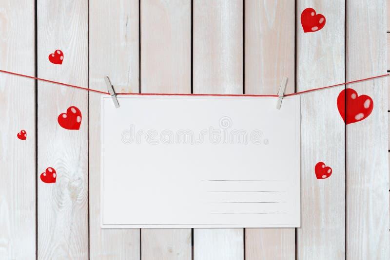 Cartolina d'auguri di San Valentino sui fili rossi circondati dai cuori su fondo bianco di legno fotografie stock libere da diritti