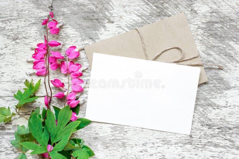 Cartolina d'auguri e busta bianche in bianco con il mazzo rosa dei wildflowers fotografia stock
