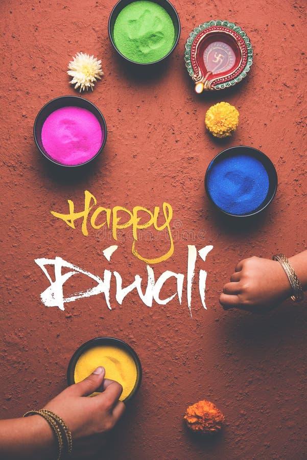 Cartolina d'auguri felice di Diwali facendo uso di Rangoli colourful in ciotole, lampada dell'argilla o di diya e scrittura felic fotografie stock libere da diritti