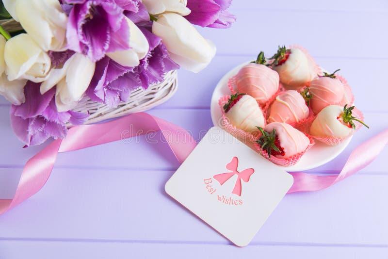 Cartolina d'auguri, fragola in cioccolato sul piatto, nastro rosa e mazzo dei tulipani porpora e bianchi sulla tavola lilla immagine stock