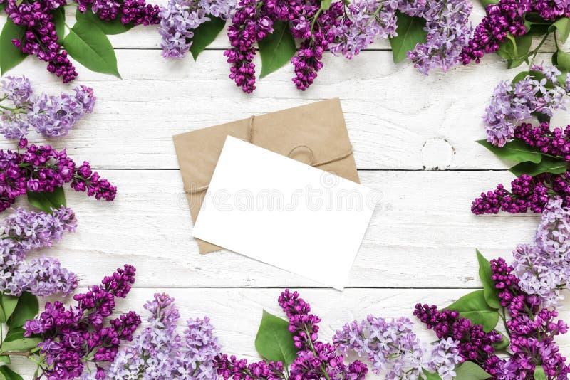 Cartolina d'auguri o invito in bianco di nozze nel telaio fatto dei fiori lilla porpora sopra la tavola di legno bianca fotografia stock libera da diritti