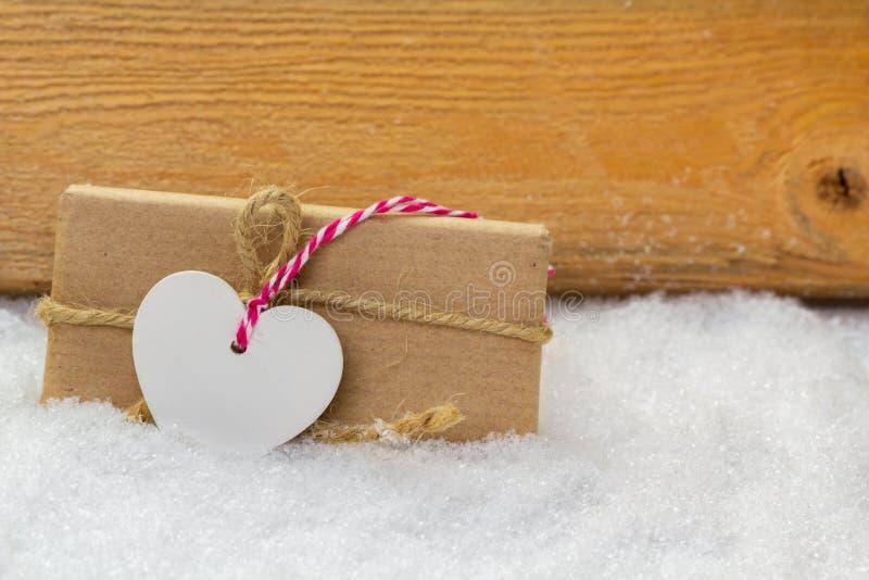 Cartolina d'auguri, regalo con cuore nella neve fotografie stock libere da diritti