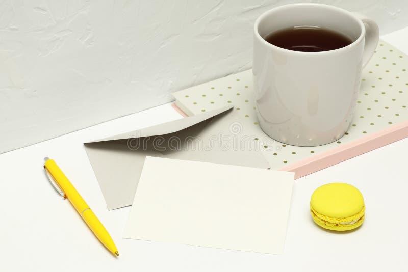 Cartolina d'auguri su un fondo bianco con le note, la busta, la penna, il macaron e la tazza di tè immagine stock