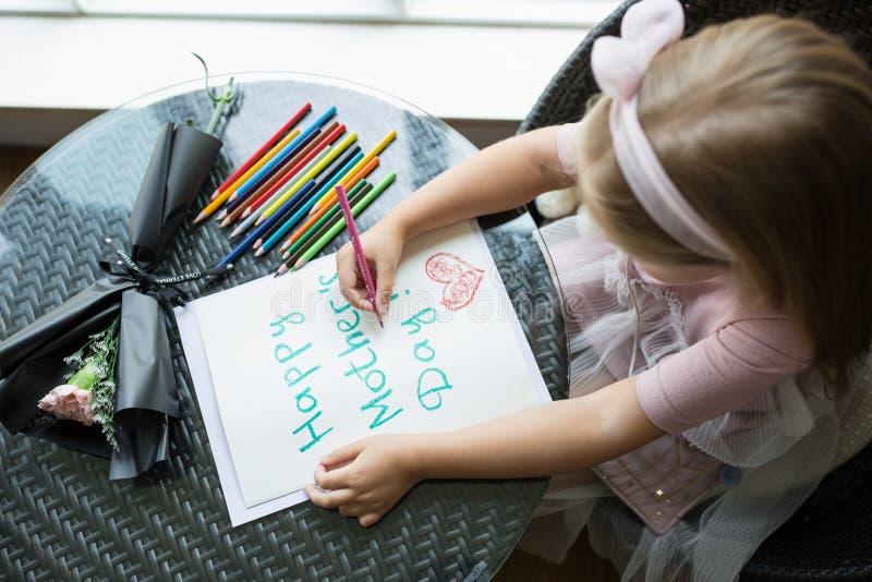 Cartolina della pittura della figlia del bambino per la mamma Ragazza che si siede a casa sulla tavola, fiore rosa dopo di menzog immagine stock libera da diritti