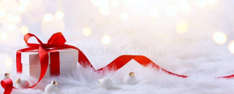 Cartolina di Natale con i contenitori di regalo e le decorazioni di Natale su un wh fotografia stock libera da diritti