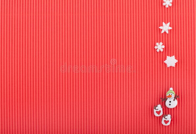 Cartolina di Natale con il pupazzo di neve, due tazze con i cuori ed i fiocchi di neve su carta ondulata rossa immagini stock