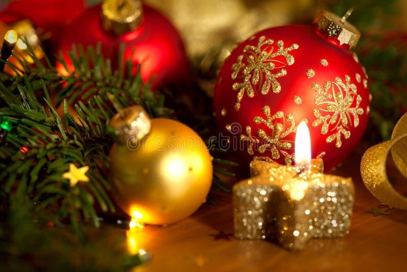 Cartolina di Natale con la candela dorata, palle, pino, luci e immagini stock