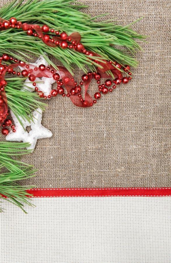 Cartolina di Natale con tela, il ramo dell'abete e la ghirlanda su tela da imballaggio fotografie stock libere da diritti