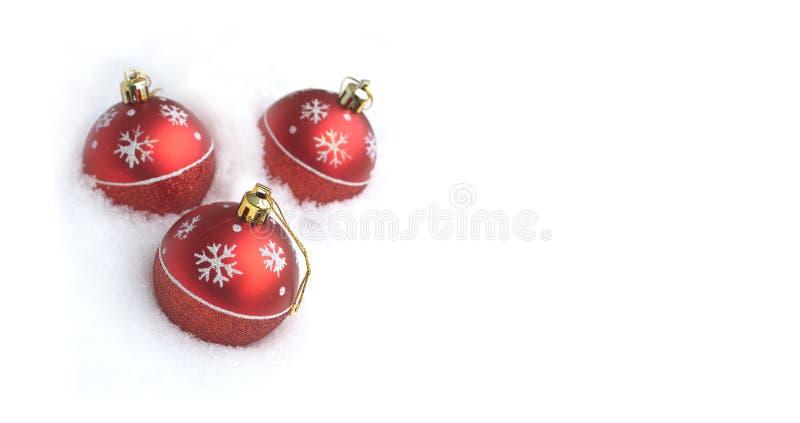 Cartolina di Natale con tre palle rosse del giocattolo fotografie stock