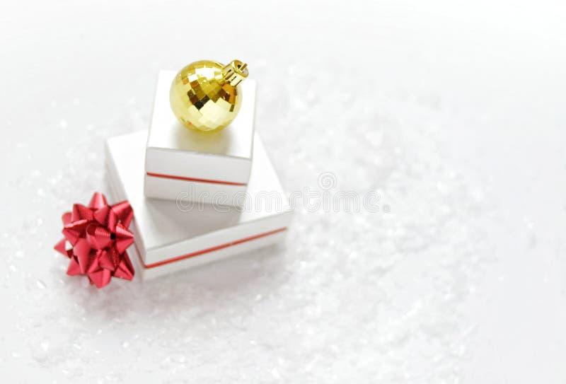 Cartolina di Natale Contenitori di regalo di Natale con un arco rosso, palla dorata di Natale, su un fondo bianco con neve immagini stock libere da diritti
