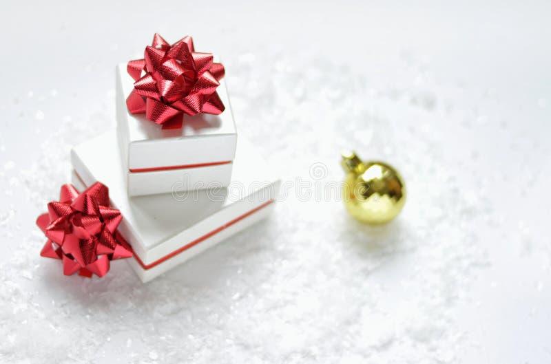 Cartolina di Natale Contenitori di regalo di Natale con un arco rosso, palla dorata di Natale, su un fondo bianco con neve immagine stock