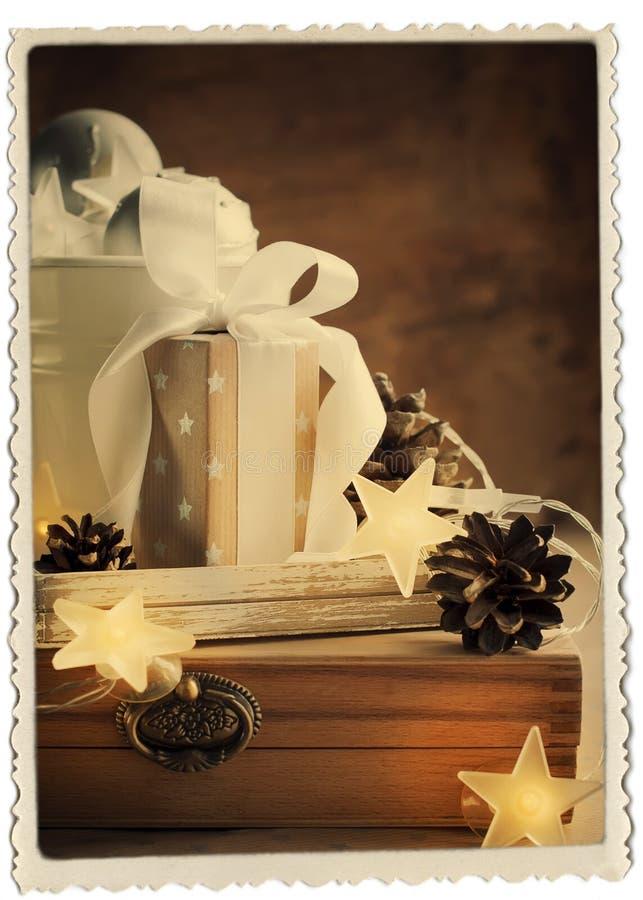 Cartolina di Natale d'annata con i regali, la scatola, il nastro bianco ed il pino co fotografie stock libere da diritti