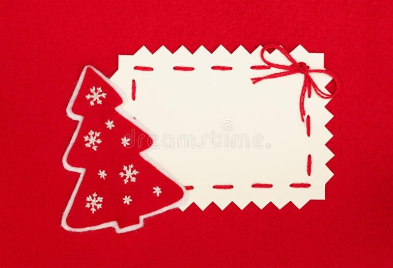 Cartolina di natale ed albero di nuovo anno su colore rosso fotografia stock