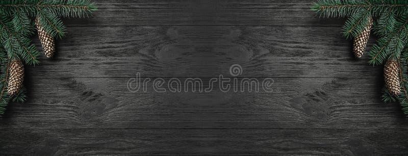 Cartolina di Natale Fondo di legno nero, con i coni di abete e di ocreanga nell'angolo, vista superiore Congratulazione di rettan immagini stock