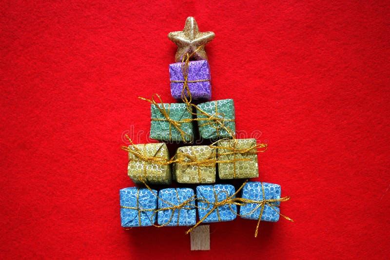 Cartolina di Natale Fondo rosso di Natale con l'albero di Natale fatto dei contenitori di regalo fotografia stock