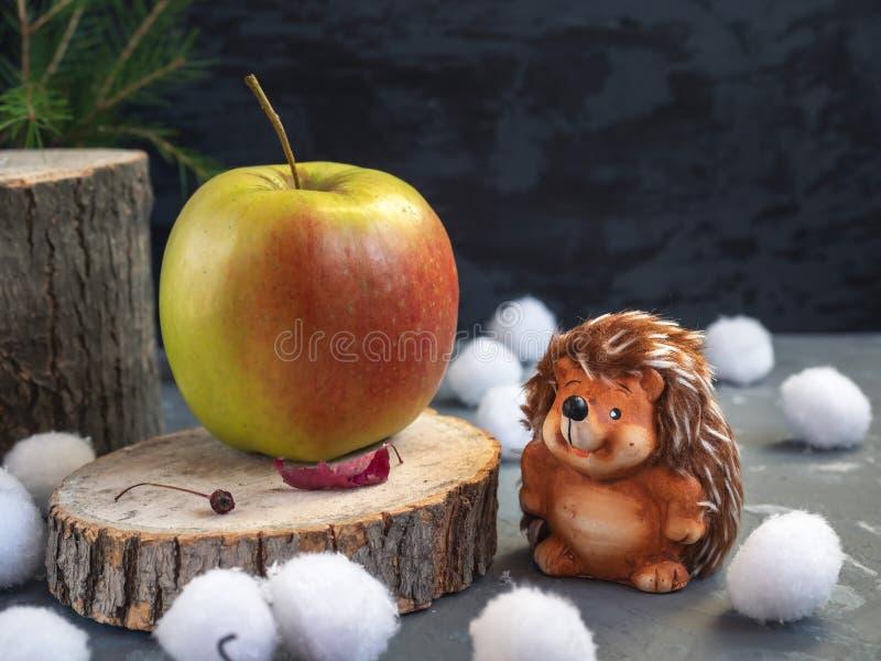 Cartolina di Natale L'istrice ha trovato una grande mela sulla canapa della foresta Palle di neve, foglie di autunno asciutte fotografia stock libera da diritti