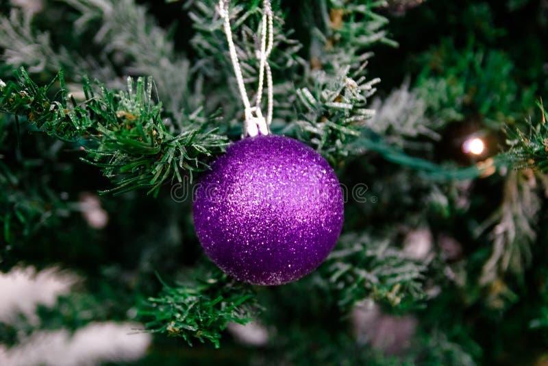 Cartolina di Natale Palla porpora di Natale sulla decorazione di treeChristmas di natale sul fondo delle scintille fotografie stock libere da diritti