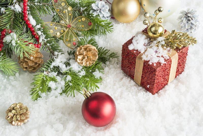 Cartolina di Natale Ramo del pino, regalo rosso, decorazione su un fondo della neve immagini stock libere da diritti
