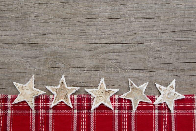 Cartolina di Natale stile country con rosso su un fondo di legno immagini stock libere da diritti