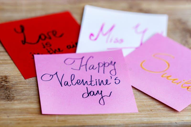 Cartoline d'auguri FELICI di rosa di giorno di biglietti di S. Valentino su un fondo di legno fotografia stock