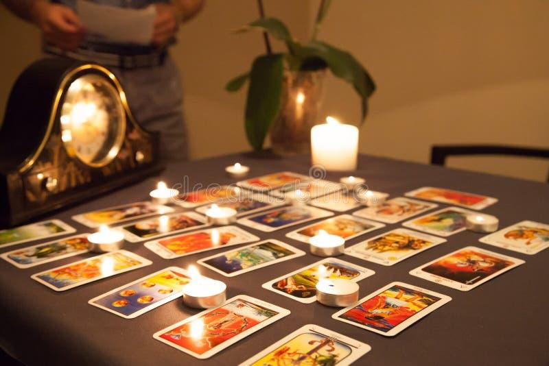 Cartomancie mystique avec les bougies et les cartes mises le feu de jouer dans d photographie stock
