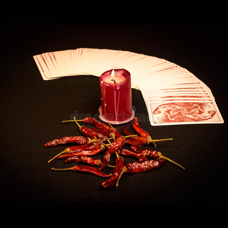 Cartomancy. In the pictured a deck of cards open fan , a red candle and red pepper dry stock image