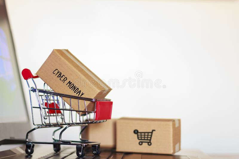 Carton box with cyber monday word and shopping cart on computer. Online shopping, e-commerce concept.  royalty free stock photography