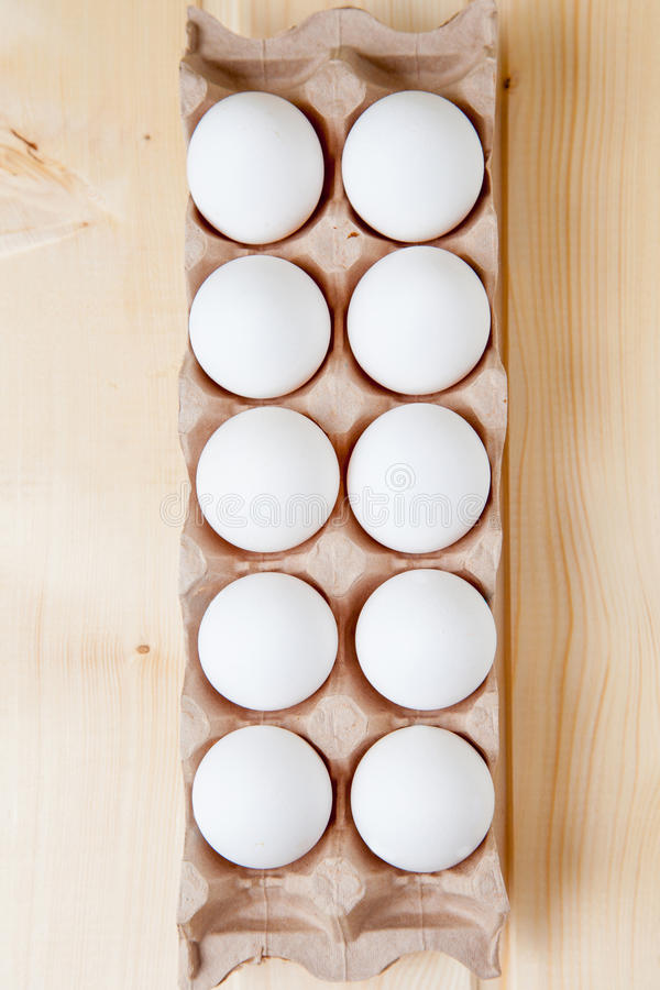 Carton box with eggs– Stock Image. Fresh farm eggs on a wooden rustic background royalty free stock images
