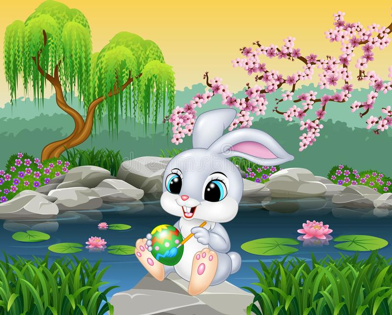 Carton happy Easter Bunny painting an egg on the rock stock illustration