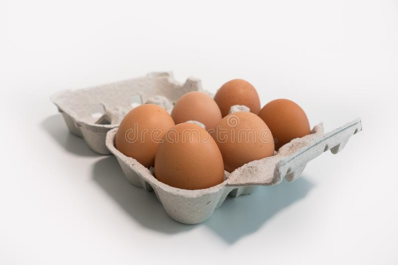 Carton of six eggs on a white table. Shallow depth of field. royalty free stock photography