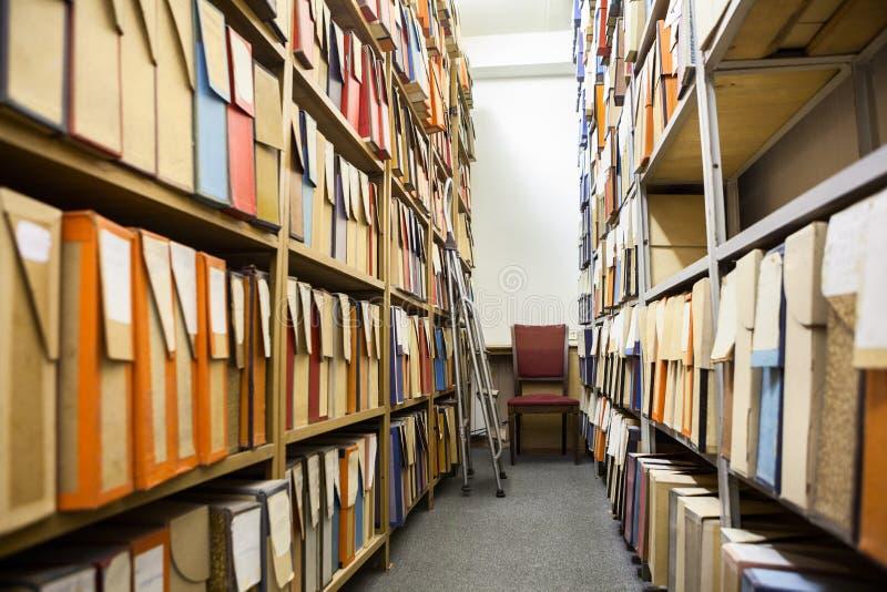 Cartonnez les boîtes pour les documents sur papier, les dessins et les disques se tenant sur les étagères en acier dans la chambr photographie stock libre de droits