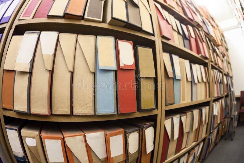 Cartonnez les boîtes pour les documents sur papier, la documentation et les disques se tenant sur des étagères dans les archives photos stock