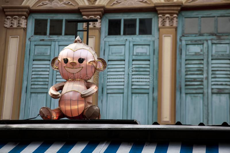 Cartoon character lamp. Scary cartoon character is sitting on narrow roof in Singapore stock photography