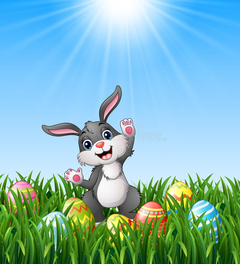 Cartoon rabbit with easter eggs in the grass royalty free illustration