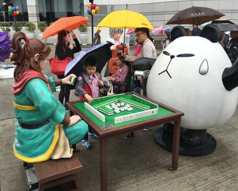 Cartoon sculptures play mahjong near the Reunification Monument, Hong Kong royalty free stock photo