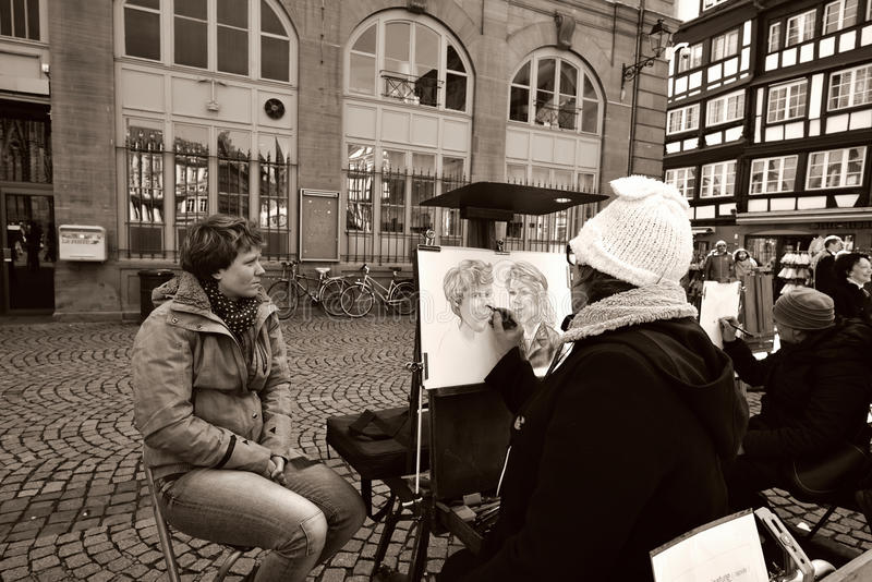Cartoonist at work on street. Artist drawing a portrait caricature for a woman on the streets of Strasbourg, France royalty free stock photos