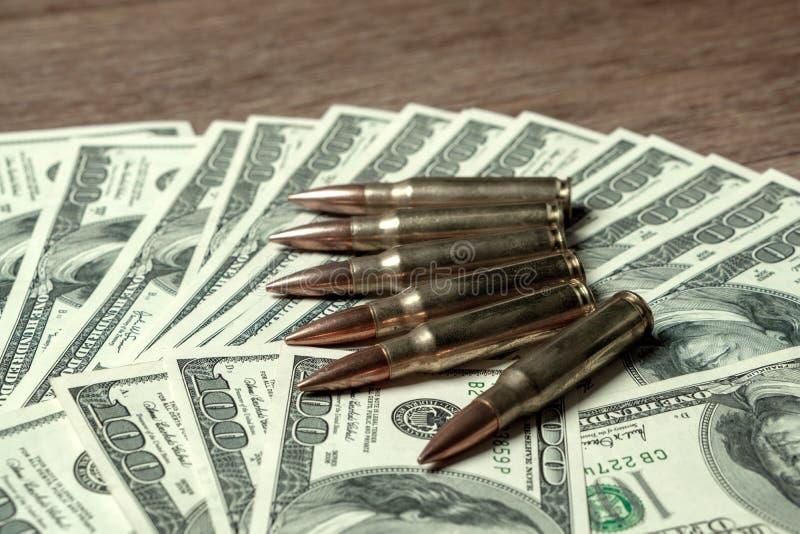 6 cartouches de fusil sur cent billets d'un dollar Concept pour le crime, massacre de contrat, assassin payé, terrorisme, guerre, images libres de droits
