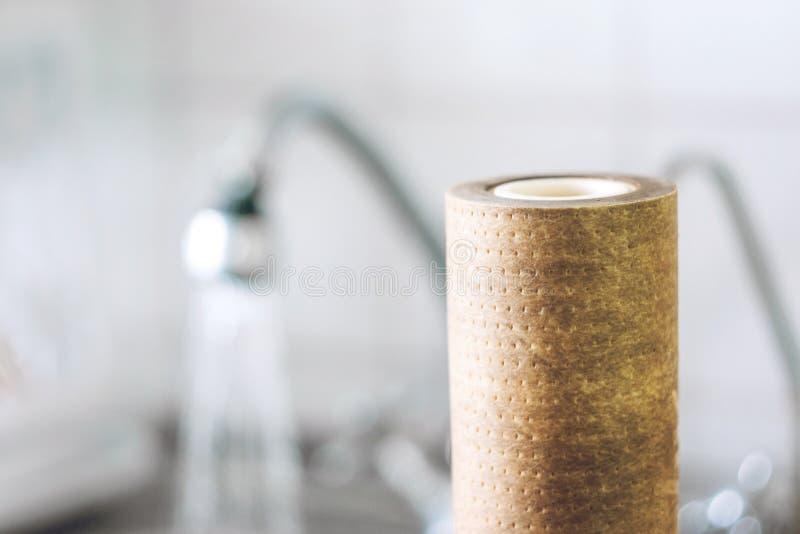 Cartouches filtrantes sales, brunes, utilisées de l'eau sur le fond de l'évier et robinet, foyer sélectif image stock