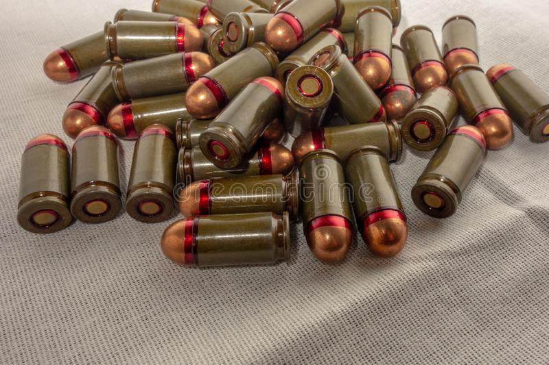 Cartridges bulk close up images. Bullets in shells for gun are piled randomly. Weapon armory concept stock photography