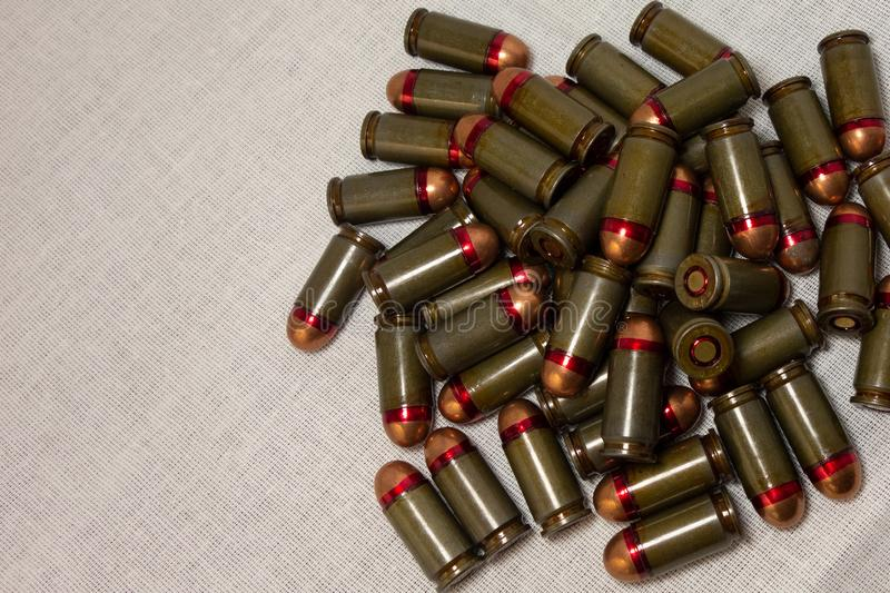 Cartridges bulk close up images. Bullets in shells for gun are piled randomly. Weapon armory concept stock image