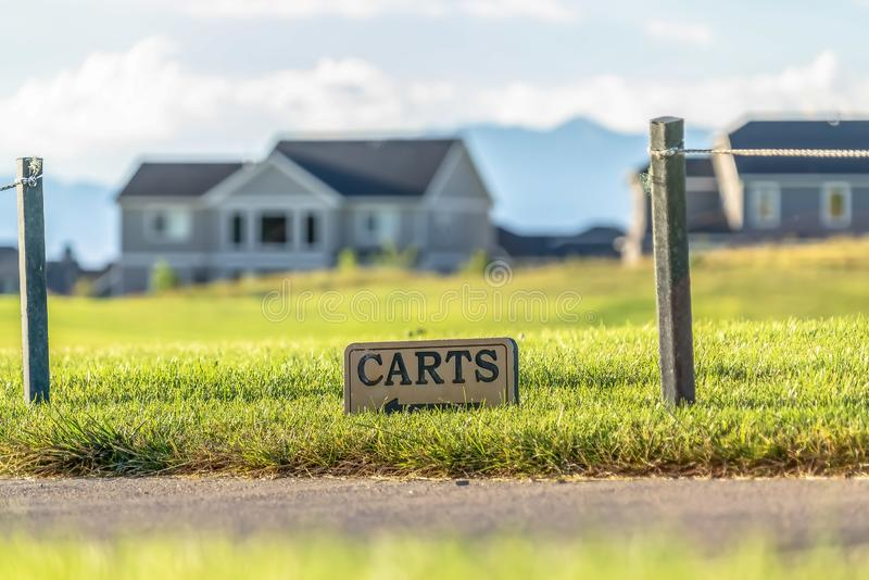 Carts sign on a grassy terrain by a road with homes and mountain background. The signage is flanked by the short posts of a rope fence royalty free stock images